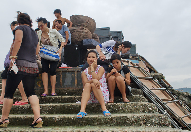 Members of a local theatre troupe wait at the ferry landing near Jingsa to be taken to one of the outer islands for a performance.