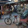A three wheel bicycle cab parked in front of a temple in Langqi Town.