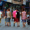 A group of youn men amble down Langqi Town's main street on a hot afternoon in August.