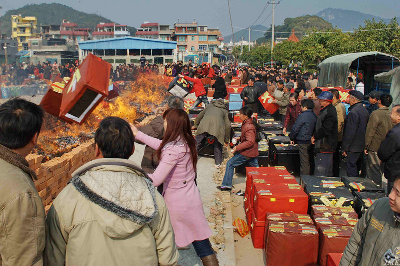 A funeral ceremony: Boxes filled with good wishes are thrown into a funeral fire.