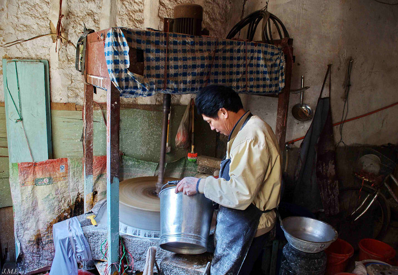 Man adding ingredients to a tofu making apparatus.