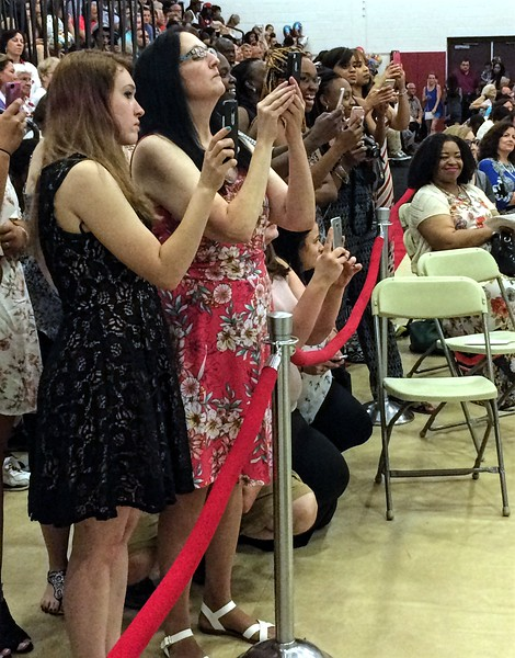 MARK ROBARGE - MROBARGE@TROYRECORD.COM<br /> Family and friends line up to snap pictures of their graduates during Lansingburgh High School's 115th Commencement on Friday night.