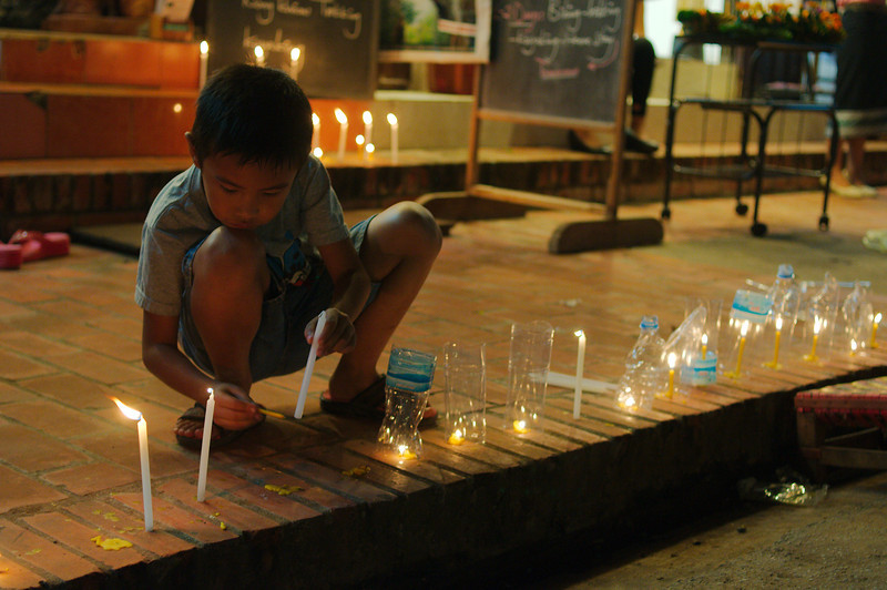 Children lighting candles outside their home