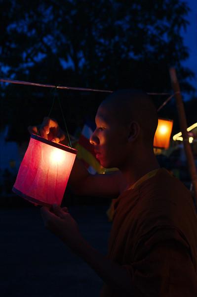A young monk lighting lanterns