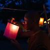 A young monk lighting lanterns