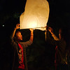 Sending off sky lanterns on the bank of the Mekong River