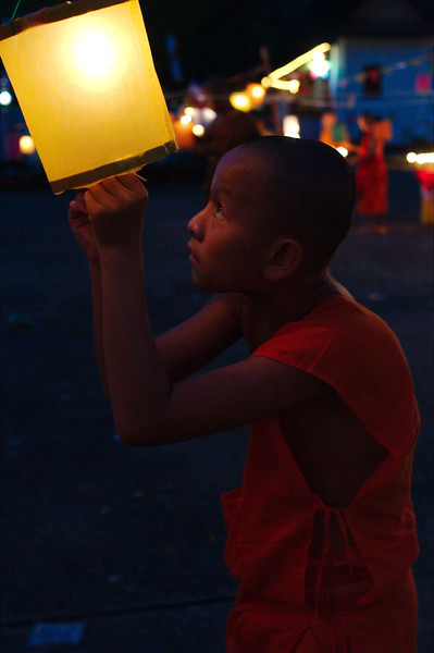 A young monk lighting festival lanterns