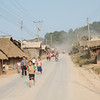 Children run home from school through the dust