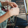 A young woman weaving in a roadside shop