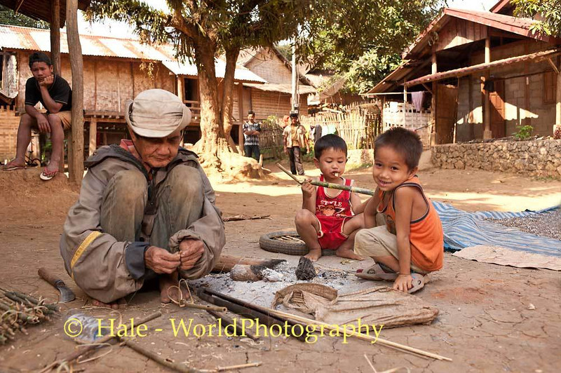 Under the Watchful Eyes of Village Children, A Khmu Man Fashions A Bird Snare