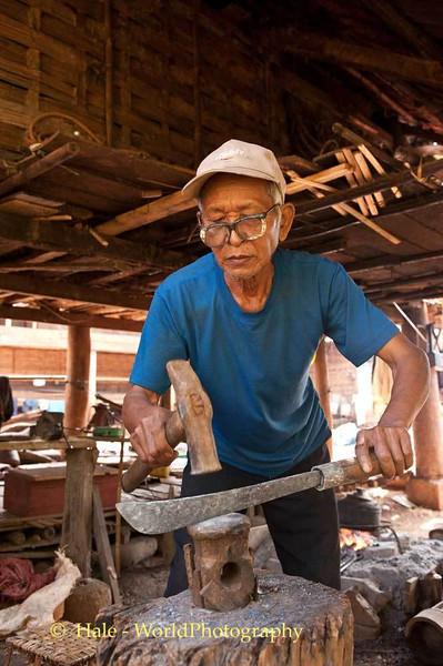 A Khmu Blacksmith Making A Knife In Laos