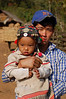 Laos, Vieng Phou Kha, Akha Trail: Father shows off his young daughter (who he dressed up in her best clothes just for the photo)