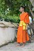 Saffron-robed Buddhist monk with a broom, Wat Sene temple, Luang Prabang, Laos