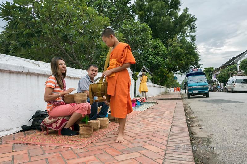 Giving alms to a Buddhist monk, Sisavong Vang Road, Luang Prabang, Laos