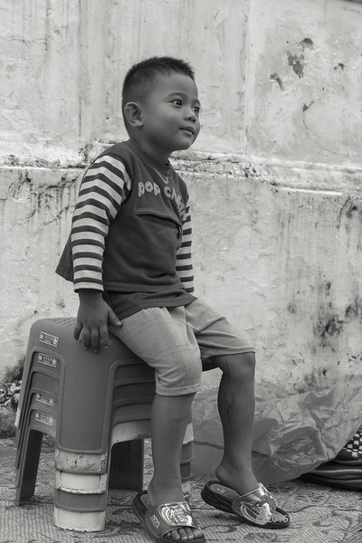 Young boy sitting on a stack of stools at the end of the alms giving ceremony BW, Wat Sene, Luang Prabang, Laos