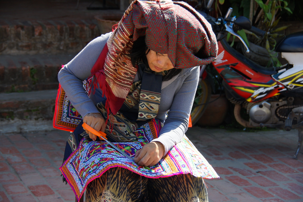 A lady wearing ethnic attire making handicrafts - Luang Prabang, Laos.  This is a travel photo from Luang Prabang, Laos.
