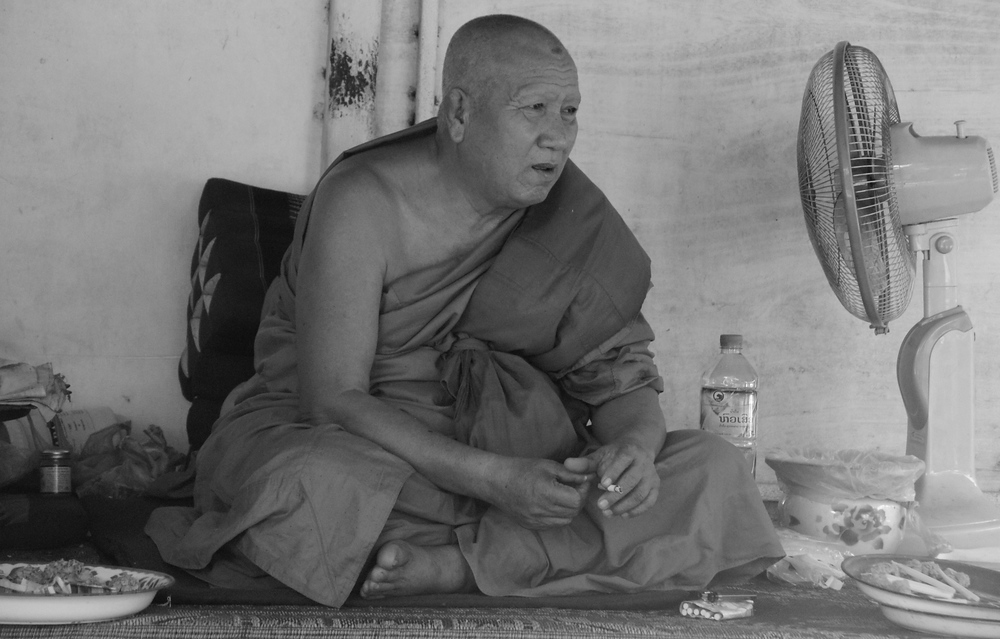 Today's daily travel photo is of Buddhist monk cooling off on a hot day in the shade with an electric fan & water bottle in Vientiane, Laos.