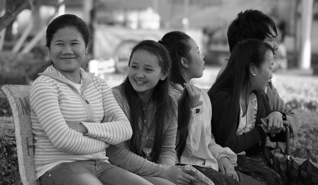 Laos ladies sitting on a park bench and smiling on a Sunday afternoon - Vientiane, Laos.  Travel photo from Vientiane, Laos.