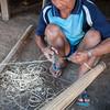 Man makes fish basket trap from bamboo, Salavan, Laos