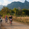 Women ride bicycles, Vang Vieng area, Laos.