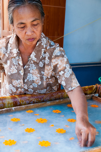 Woman adds flowers to paper, Ban Xang Khong, Luang Prabang, Laos