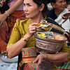 Woman waits to give monks alms at That Luang festival, Vientiane, Laos.
