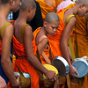 Buddhist monks receive alms at That Luang festival, Vientiane, Laos.