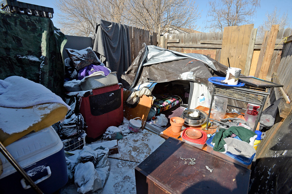 . A makeshift home including a bed under tarps, clothing and dishes are hidden behind a privacy fence at 860 4th St. SE in unincorporated Loveland on Monday, Feb. 11, 2019. Larimer County deemed the two buildings on the property to be a threat to public safety because of code violations including hazardous levels of methamphetamines.   (Photo by Jenny Sparks/Loveland Reporter-Herald)