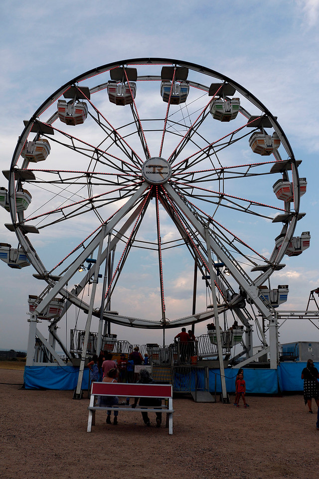 Maggie Little of Fort Collins and Ellen Luster of Loveland sit on a bench Friday, August 4, 2017 at the Larimer County Fair as their families ride the ferris wheel. (Michelle Risinger/ Loveland Reporter-Herald)