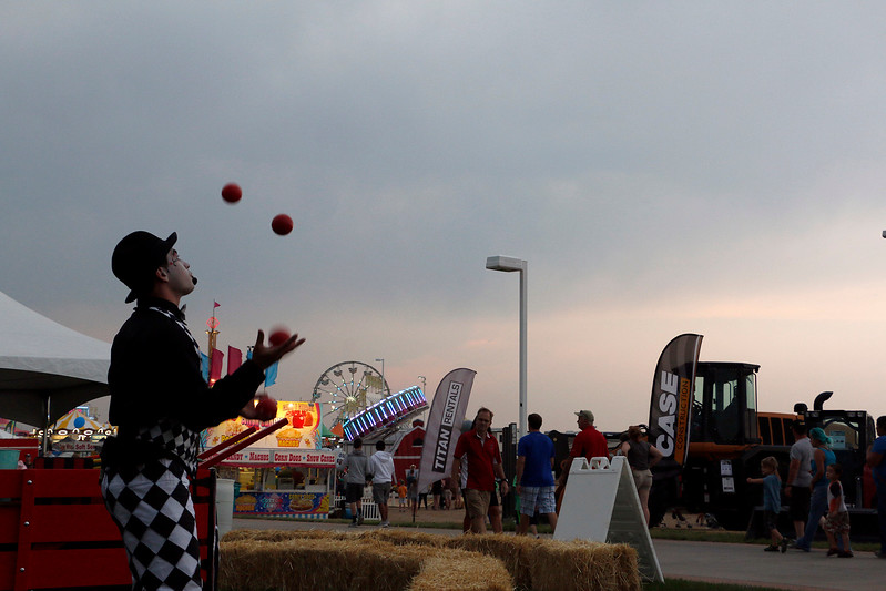 Alex Bistrevsky of Stilt Circus Interactive Circus Station passes time Friday, August 4, 2017 at the Larimer County Fair by juggling. (Michelle Risinger/ Loveland Reporter-Herald)