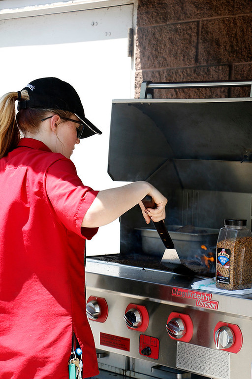 . Ali Hensel mans the grill Wednesday, August 2, 2017, for concessions at Larimer County Fair. (Michelle Risinger/ Loveland Reporter-Herald)