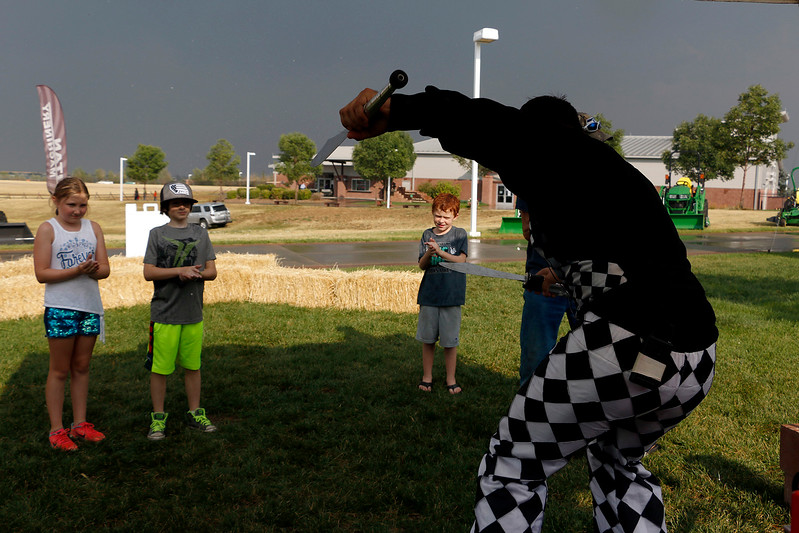 Alex Bistrevsky juggles knives while on a balance board Friday, August 4, 2017 before teaching the children in front of him how to balance on the board themselves. Bistrevsky is part of Stilt Circus who had an interactive circus station at Larimer County Fair. (Michelle Risinger/ Loveland Reporter-Herald)