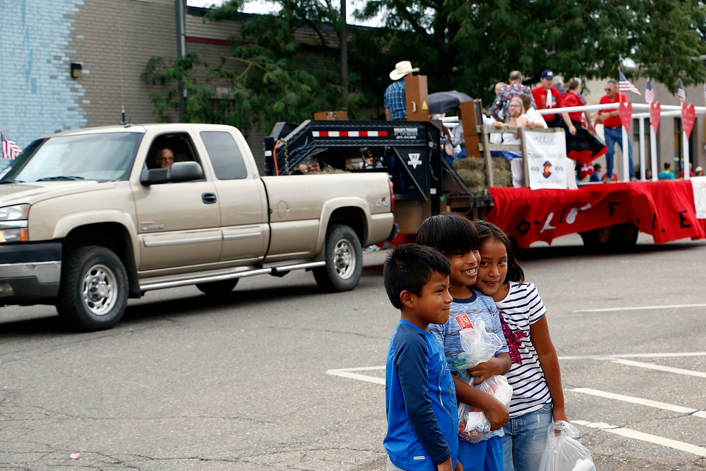 . Marcus Fisher, 6, right, Zander Fisher, 9, center and Christina Fisher, 9, left, smile for the camera Saturday, July 29, 2017, as the floats go by at the Larimer County Fair Parade in Loveland. (Michelle Risinger/ Loveland Reporter-Herald)