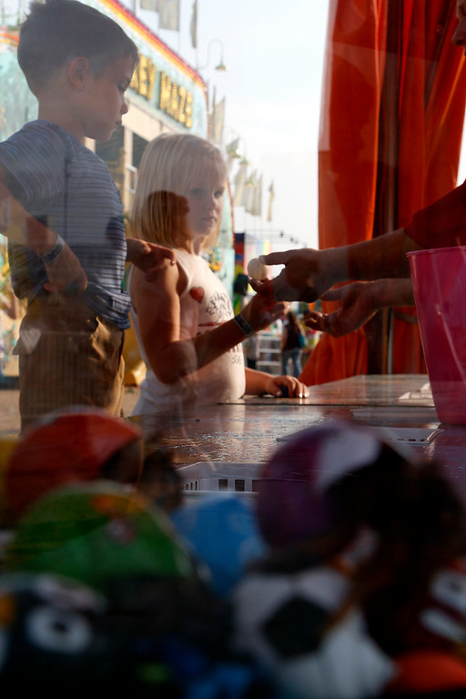 . Deegan Winterbottom, 5, left, and Annabelle Winterbottom, 7,  right, toss ping-pong balls Friday, August 4, 2017 at the Larimer County Fair for the chance to win a goldfish, betta fish, or hermit crab. (Michelle Risinger/ Loveland Reporter-Herald)