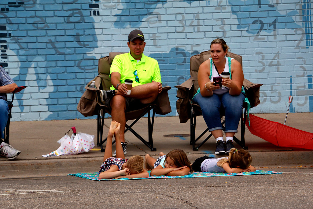 . The Kilker family get comfy Saturday, July 29, 2017 as they wait for the Larimer County Fair Parade to begin. The girls were most excited to see the dancing horses. (Michelle Risinger/ Loveland Reporter-Herald)