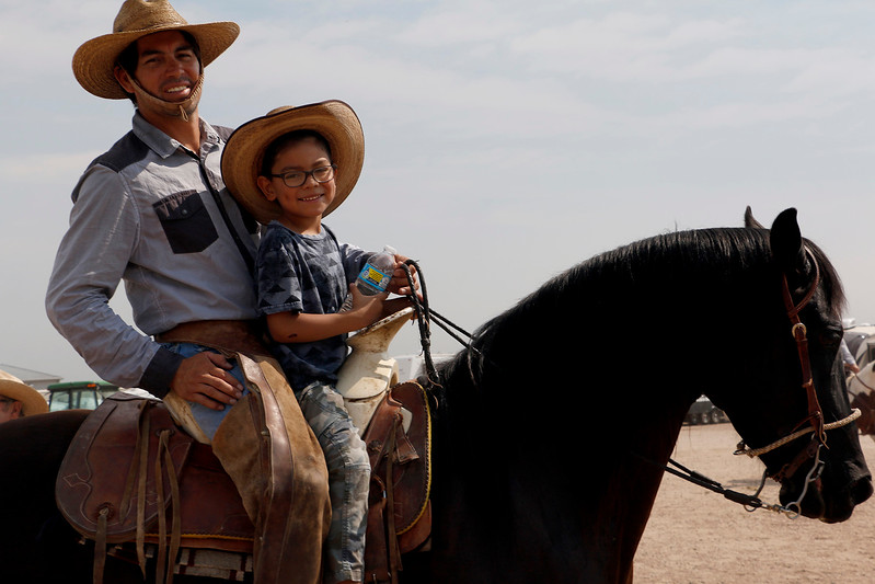 José Jaurez and his son, Nicholas Juarez, 6, ride on the back of Blackstar Saturday, August 5, 2017 during the mounted shoot at the Larimer County Fair. (Michelle Risinger/ Loveland Reporter-Herald)