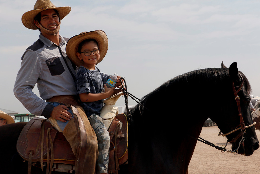. José Jaurez and his son, Nicholas Juarez, 6, ride on the back of Blackstar Saturday, August 5, 2017 during the mounted shoot at the Larimer County Fair. (Michelle Risinger/ Loveland Reporter-Herald)