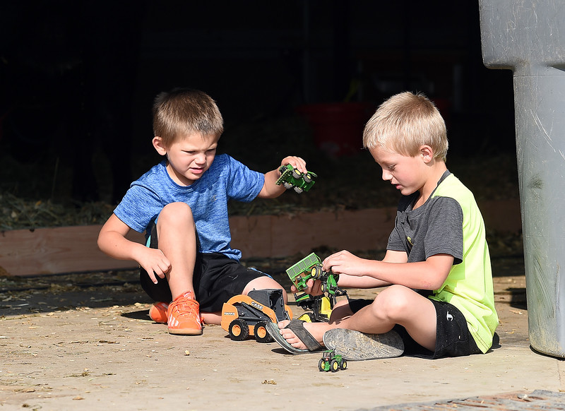 Kahl Starck, 3, left, and his brother, Sawyer Starck, 5, play with their tractors and other toys near a bay door in the beef barn Monday, Aug. 6, 2018, during the Larimer County Fair at The Ranch in Loveland.  (Photo by Jenny Sparks/Loveland Reporter-Herald)