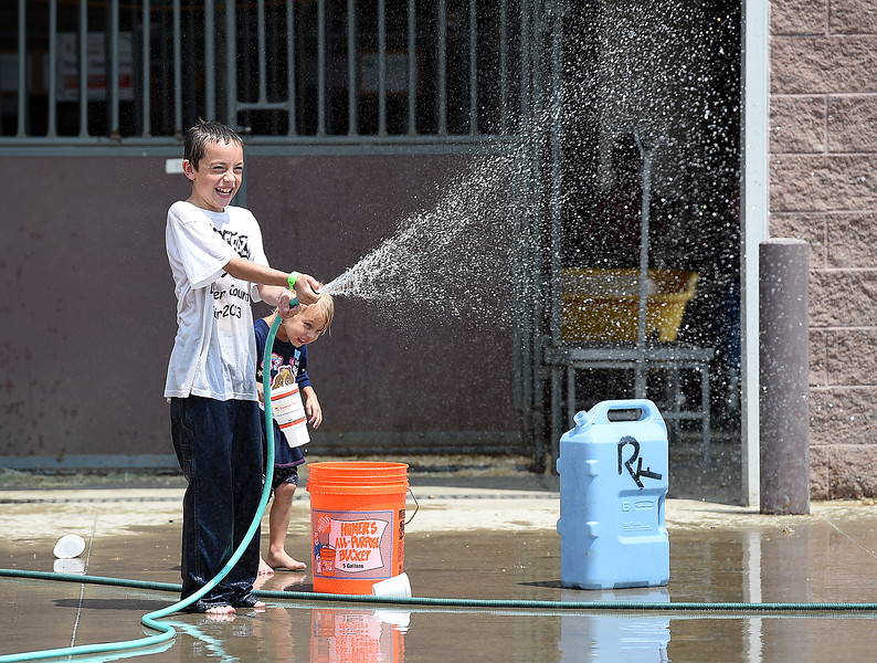 Brayden Rinebarger, 11, sprays other kids with Nessa Crocker, 4, by his side, during a water fight outside the barns on Monday, Aug. 6, 2018, during the Larimer County Fair at The Ranch in Loveland.  (Photo by Jenny Sparks/Loveland Reporter-Herald)