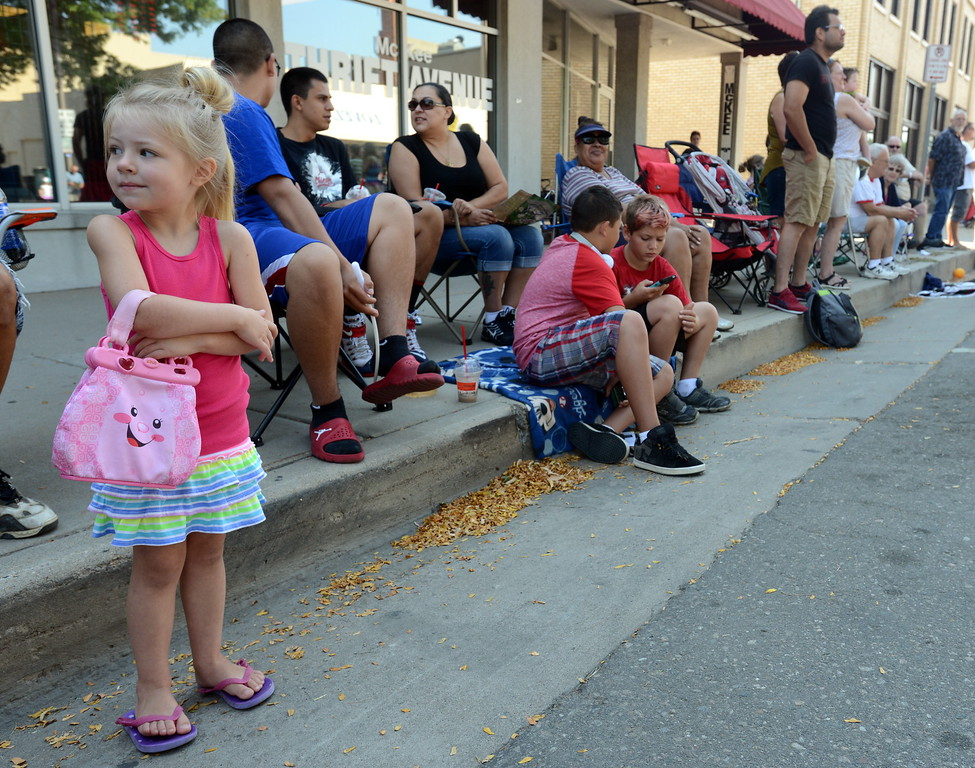 Four-year-old Isobelle Trujillo of Loveland keeps an eye out for candy during the Larimer County Fair Parade through downtown Loveland on Saturday morning, July 30, 2016. Her grandmother, Colleen Trujillo, said Isobelle brought her pink purse to hold any candy thrown by parade participants. (Photo by Craig Young / Loveland Reporter-Herald)