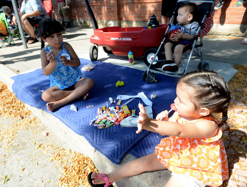 Two-year-old Sydney Sierra of Greeley uses one hand to wave and the other to hold a sucker during the Larimer County Fair Parade in downtown Loveland on Saturday morning, July 30, 2016. Sydney and her sister Langston, 4, left, accumulated quite a stash of candy during the parade, which they watched with their brother, Silas, 1, in stroller, and parents, Denise and Al. (Photo by Craig Young / Loveland Reporter-Herald)