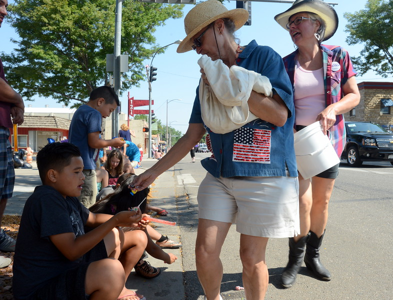 Sally Carlson, a volunteer with Hugh McKean's campaign for the Colorado House, drops candy into the hands of Loveland resident Alex Herrera, 11,  during the Larimer County Fair Parade in downtown Loveland on Saturday morning, July 30, 2016. Alex was watching the parade with his brothers, Cristian, 8, and Anthony, 7, and his 10-year-old cousin, Kimberly Herrera.  (Photo by Craig Young / Loveland Reporter-Herald)