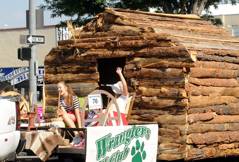Members of the Wranglers 4-H Club ride with their log cabin in the Larimer County Fair Parade through downtown Loveland on Saturday morning, July 30, 2016. (Photo by Duncan Young / for the Reporter-Herald)