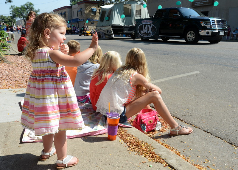 "McKenzie Whitman, 2 1/2, tirelessly waves at every float in the Larimer County Fair Parade in downtown Loveland on Saturday morning, July 30, 2016. McKenzie was watching the parade with her cousins, on the curb, her parents, Jessica and Derek, and her brothers, Wyatt, 4, and Owen, 10 months. Her mom was the fair and rodeo queen in 2004, when her name was Jessica Benish. ""They're excellent memories. I loved it,"" said Jessica, a former Loveland resident who now lives in Wellington. (Photo by Craig Young / Loveland Reporter-Herald)"
