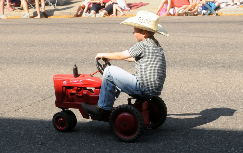 A boy pedals a toy tractor during the Larimer County Fair Parade through downtown Loveland on Saturday morning, July 30, 2016. (Photo by Duncan Young / for the Reporter-Herald)