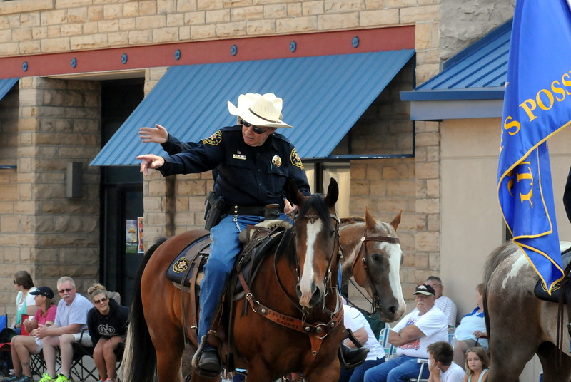 Members of the Larimer County Sheriff's Posse wave to the crowd during the Larimer County Fair Parade through downtown Loveland on Saturday morning, July 30, 2016. (Photo by Duncan Young / for the Reporter-Herald)