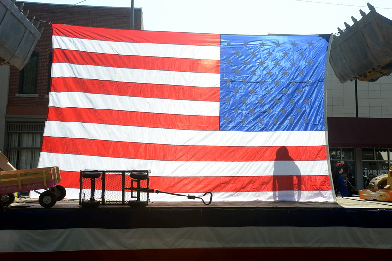 A rider on the A Concrete Inc. float is silhouetted through a giant American flag during the Larimer County Fair Parade in downtown Loveland on Saturday morning, July 30, 2016. (Photo by Craig Young / Loveland Reporter-Herald)