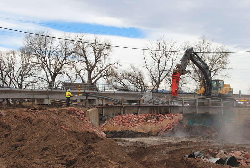 Construction crews tear down a bridge over County Road 15 south of Berthoud on Tuesday, Jan. 30, 2018. A new bridge will be installed as part of the $1.9 million project, which is one of several road and bridge projects underway this winter for permanent repairs after the 2013 flood. (Pamela Johnson / Loveland Reporter-Herald)