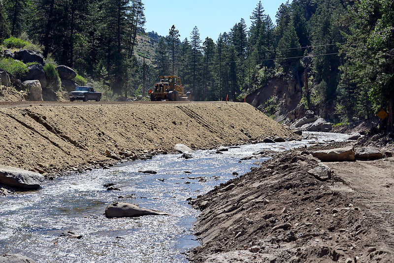 Drivers share County Road 43 with construction equipment Thursday, July 14, 2016, after the road reopened west of Loveland. The road, which was damaged during the flood in 2013, was raised farther above the river and in some areas was relocated to prevent damage in case of another flood. (Photo by Jenny Sparks/Loveland Reporter-Herald)