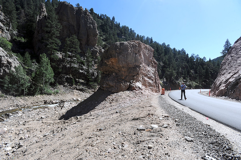 Larimer County Commissioner Steve Johnson walks along County Road 43 taking photos near Monument Rock, at left, on Thursday, July 14, 2016, west of Loveland between Drake and Glen Haven. The road, which was heavily damaged during the Septmeber 2013 flood, re-opened Thursday with a ribbon cutting by county officials. To prevent further damage from another flood, crews moved the road to the other side of Monument Rock.  (Photo by Jenny Sparks/Loveland Reporter-Herald)
